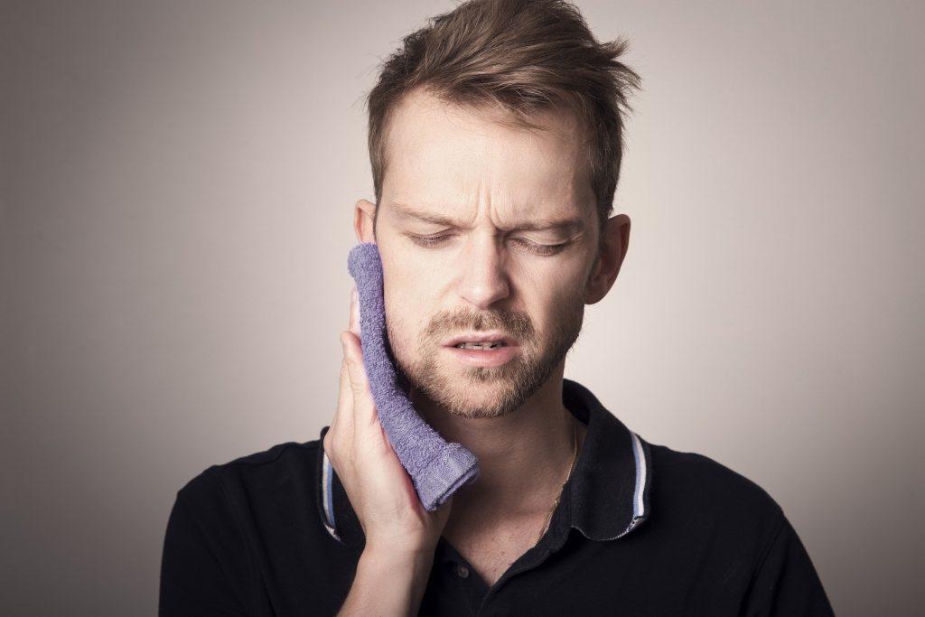 Mann hält Waschlappen an Wange wegen Zahnschmerzen durch Parodontitis